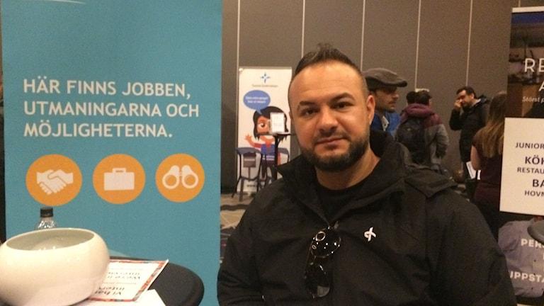 Jobbsökande Mohammed står i en mässhall där företag och jobbsökande möts