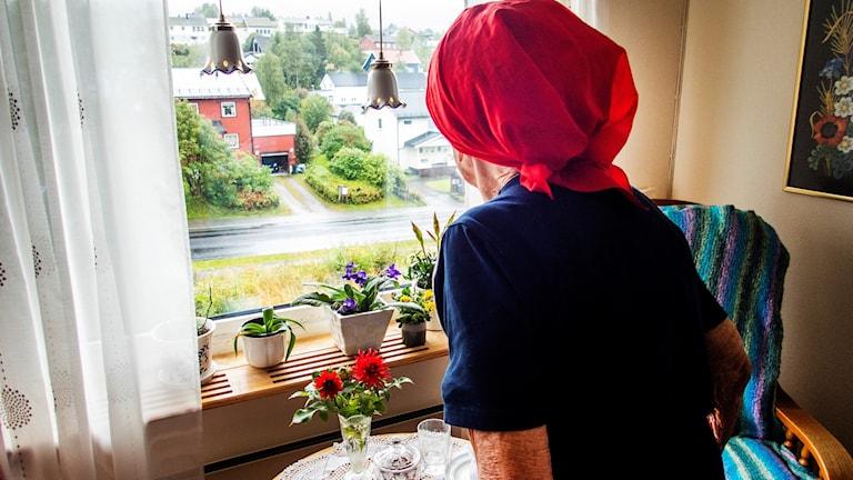 Äldre kvinna tittar ut genom fönstret