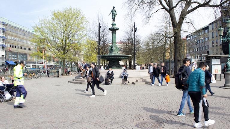 Brunnsparken med statyn i mitten och folk som går.
