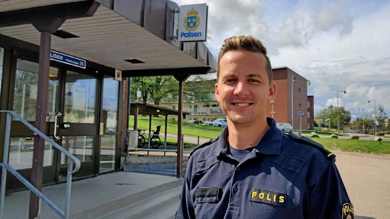 Christian Nordén står framför polishuset i uniform. Han ser glad ut och det är soligt och grönt ute.