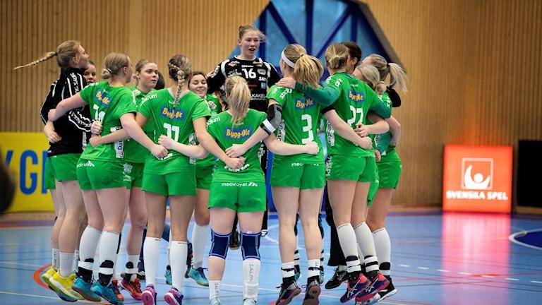 Ett handbollslag i grönt matchställ kramar varandra.