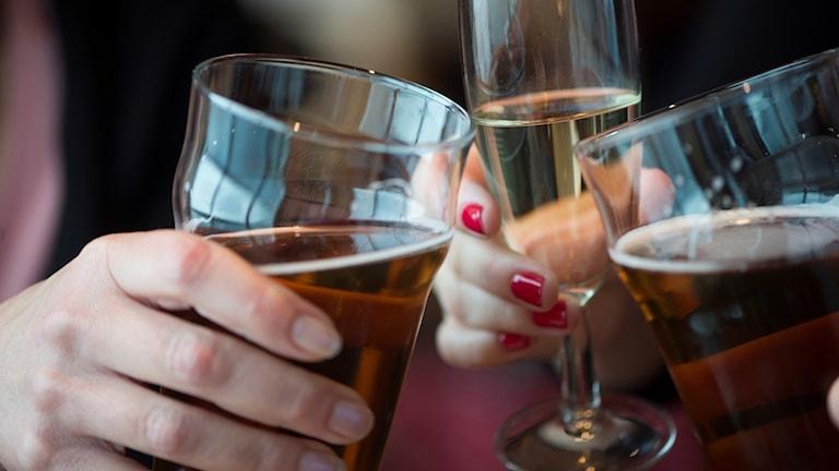 Vuxna människor skålar i glas med öl och vin.