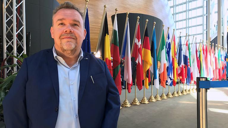 En man i blå kavaj och ljusblå skjorta. Bakom honom syns en flaggor från alla EU:s medlemsländer.