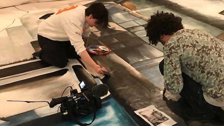 Nikita Kihlander målar tillsammans med sin konstnärshandledare Gilson Serafin.