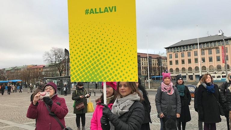 Kvinnor står på ett torg med plakat i olika färger. På plakaten står de ol,ika hashtaggar som yrkesgrupper skrivit under sina #metoo-upprop med.