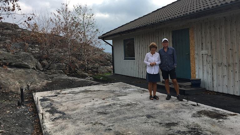Lars Gunnar och Anette Karlsson står på cementplattan som finns kvar efter garaget.