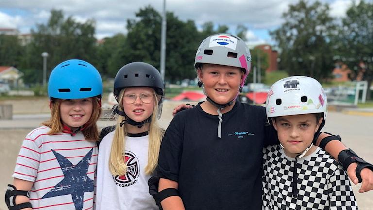 Fyra barn med hjälmar på en skatepark.