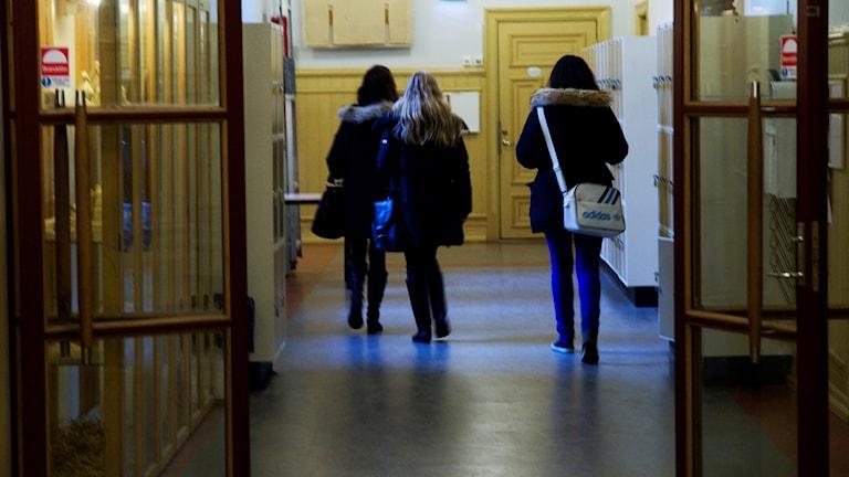 korridor i gymnasieskola med tre elever