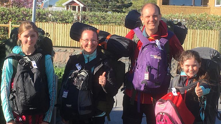 En familj med två barn som har ryggsäckar