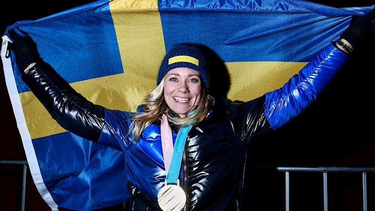 Frida Hansdotter med stor guldmedalj runt halsen håller upp en svensk flagga. Foto: Pontus Lundahl/TT