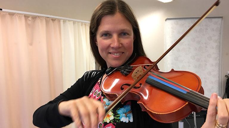 Christel Weiner spelar på en fiol med färger vid strängarna.