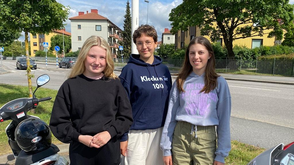 Tre tjejer framför en moped.