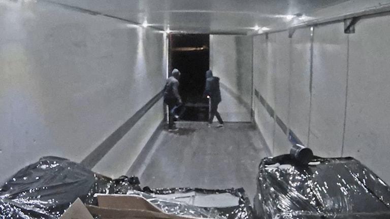 Två maskerade rånare står inne i lastbilen med bakdörren öppen.