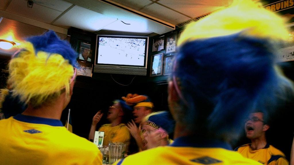 Svenska supporters tittar på en match på en krog.