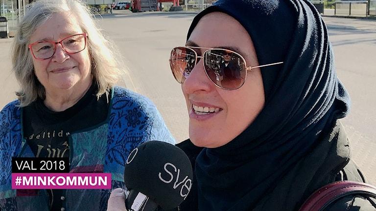 Två kvinnor intervjuas. En äldre med gråfärgat hår och en yngre med svart sjal på huvudet.