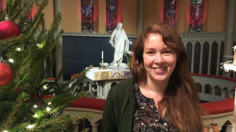 En kvinna med långt brunt hår står i kyrkan bredvid en julgran.