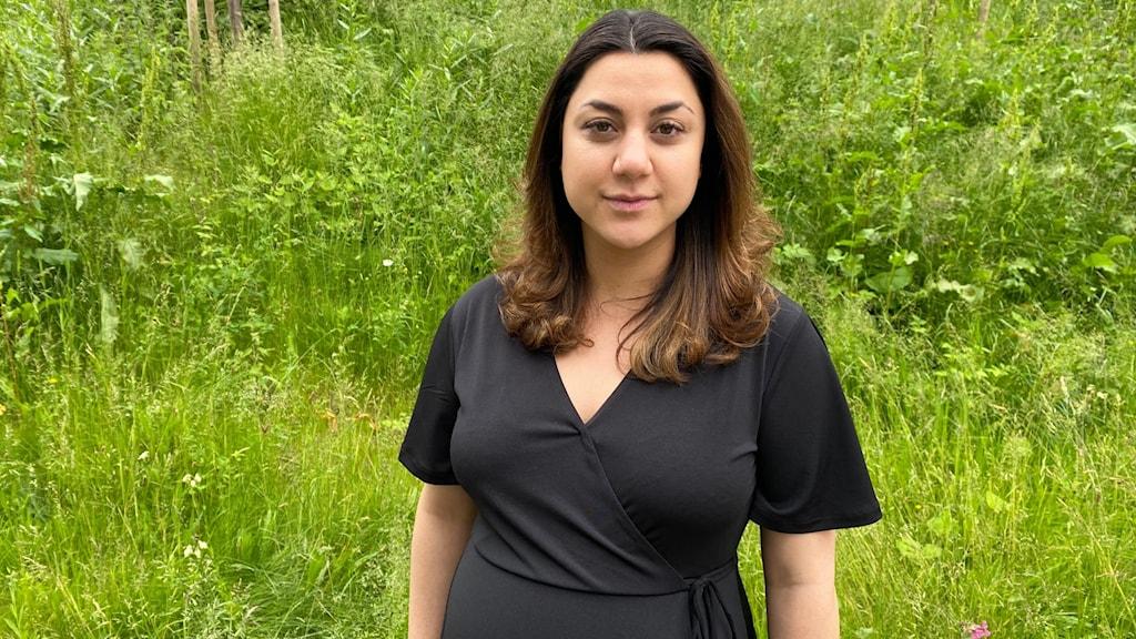 Kvinna klädd i svart mot grön bakgrund.