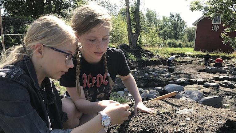 Noa Lind och Nora Rutland testar på det arkeologiska arbetet.