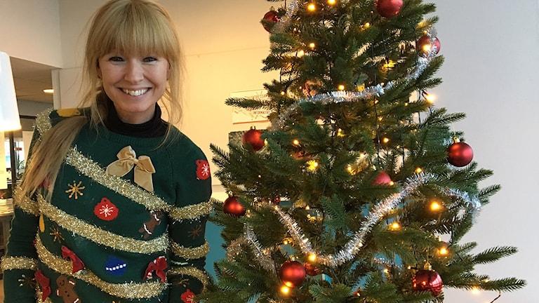 En kvinna klädd i en grön tröja med julpynt på hon står bredvid en julgran.