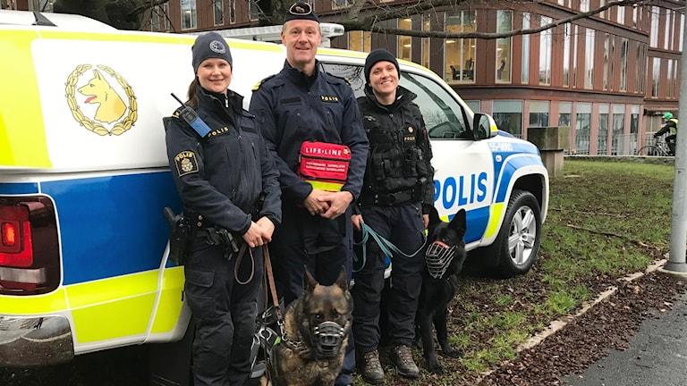 Hundförare och hundar framför den nya polisbilen. En man håller en hjärtstartare.