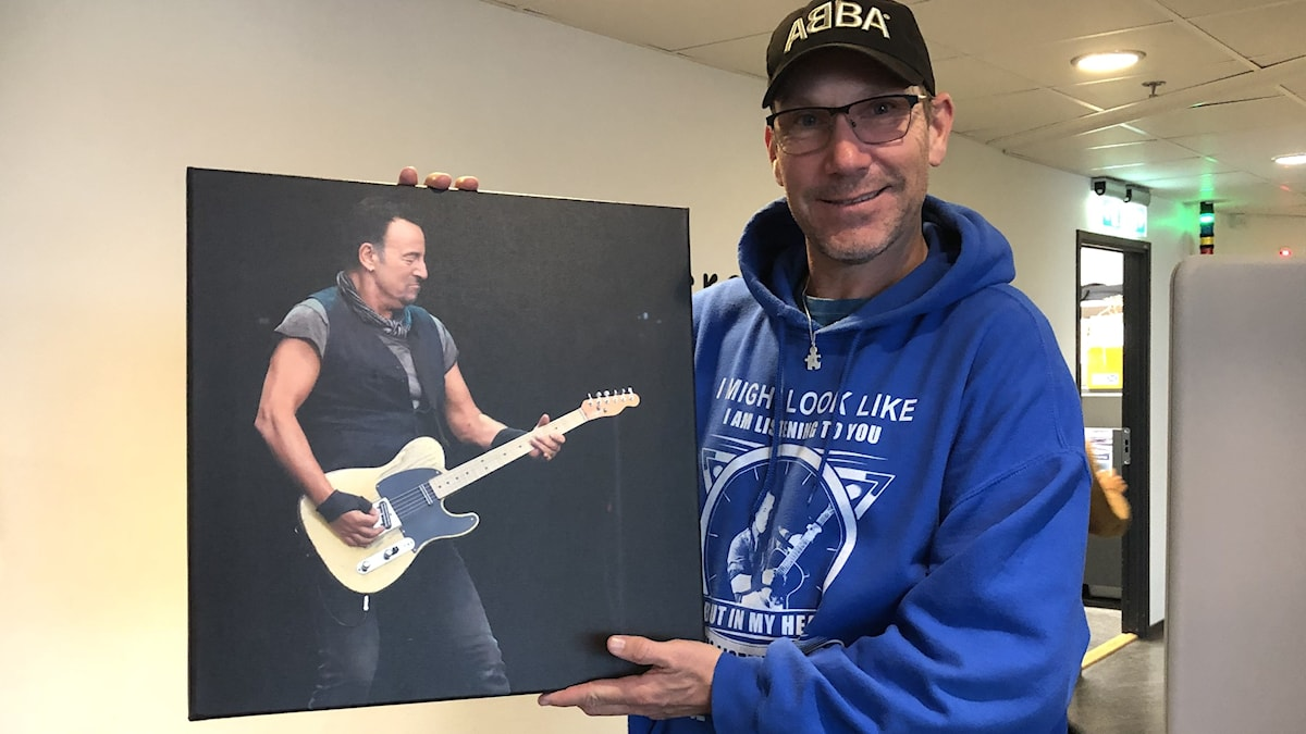 En man håller upp en fototavla med Bruce Springsteen på.