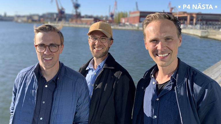 De tre bröderna står med havet i bakgrunden. Man ser lite kranar och industri längre bort. De ser glada ut.