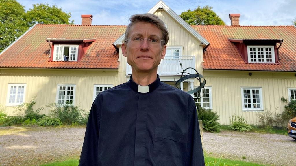 Man i svart prästskjorta framför stort gult hus med gröna träd och blå himmel.