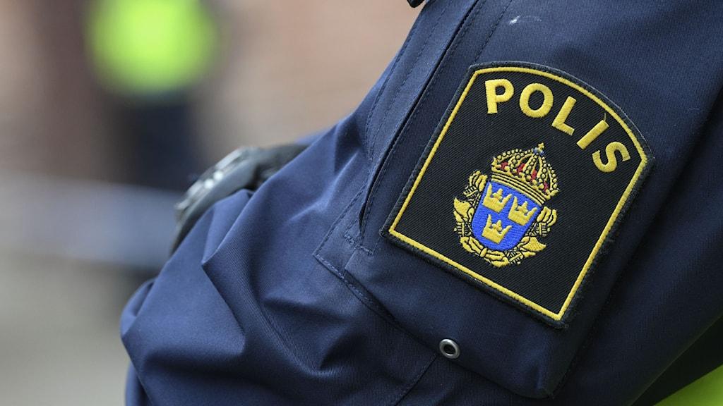Polisens logotyp på en polismans arm.