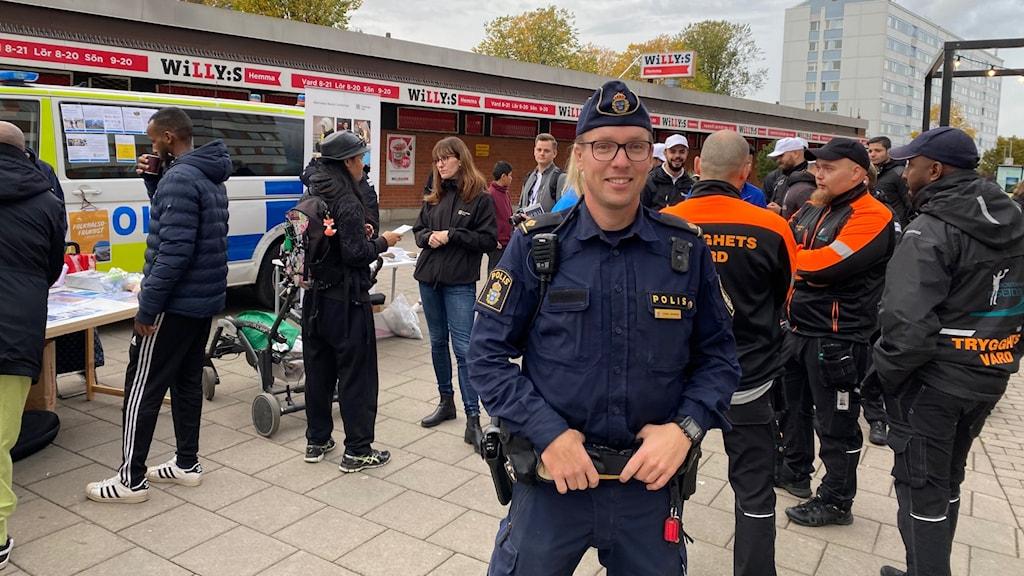 En polis framför en folksamling.
