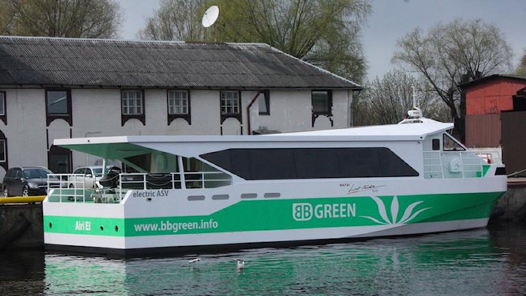 En grönvit färja för passagerare och cyklar