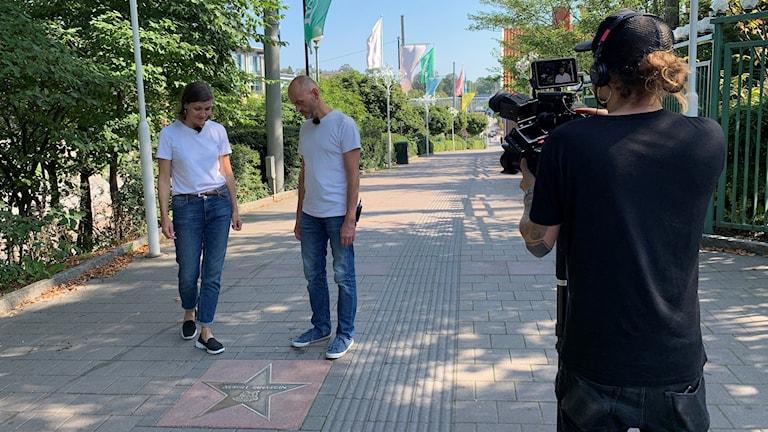 En man och en kvinna iklädda jeans och vita tröjor tittar ned på en stjärna på promenadstråket. En man till höger i bild håller i en filmkamera riktat mot paret.