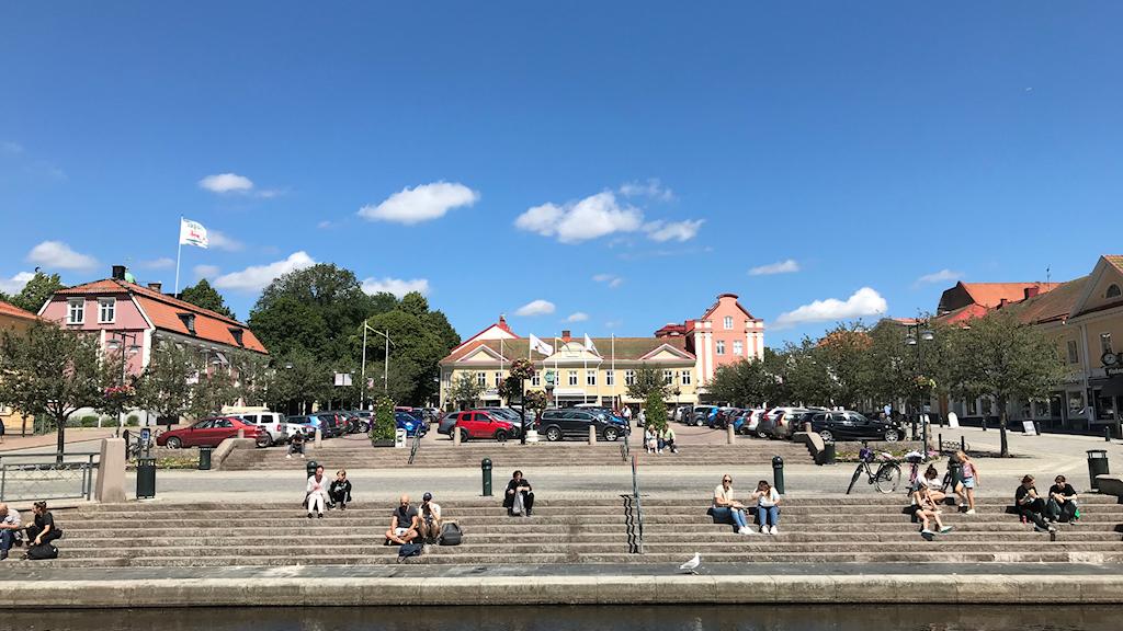 Bild på Stora torget i Alingsås, med människor som sitter i trappen ned mot Lillån.