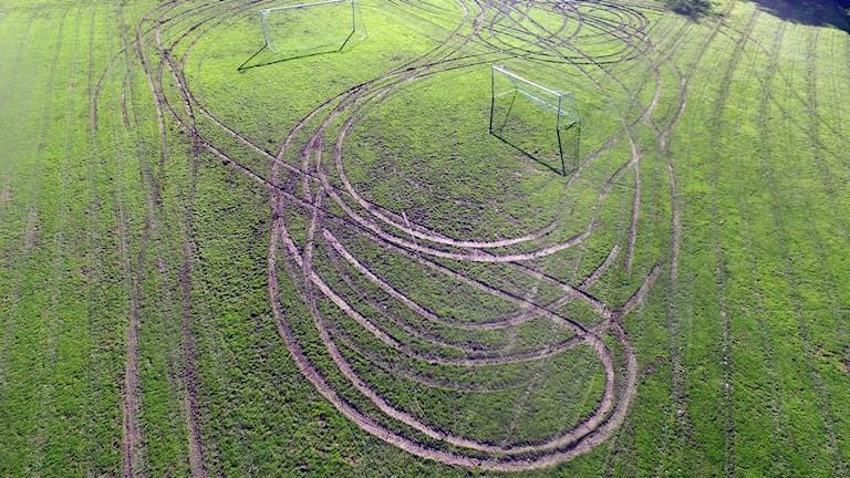 En gräsplan med stora och djupa hjulspår.