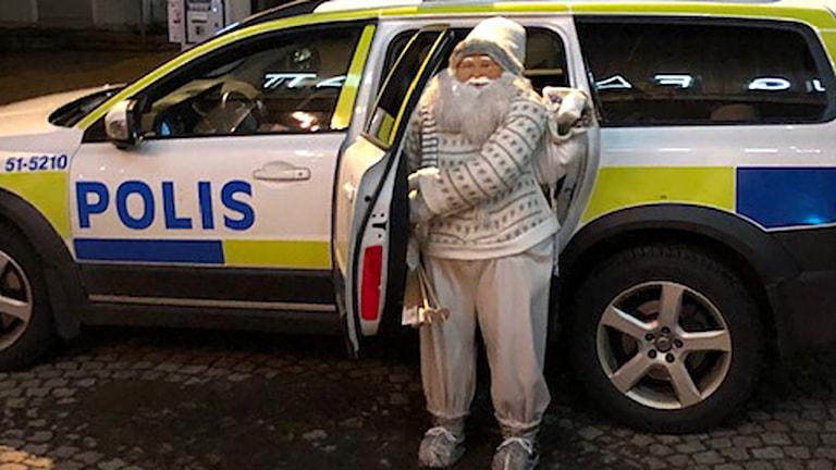 En stor Jultomte-figur åker polisbil.