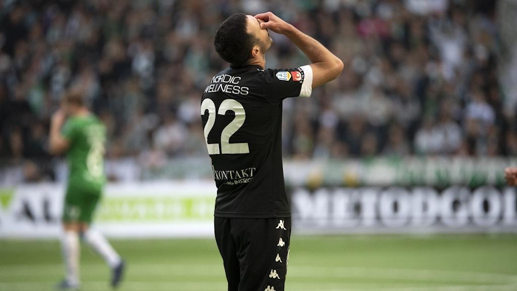 En fotbollsspelare håller händerna för ansiktet.