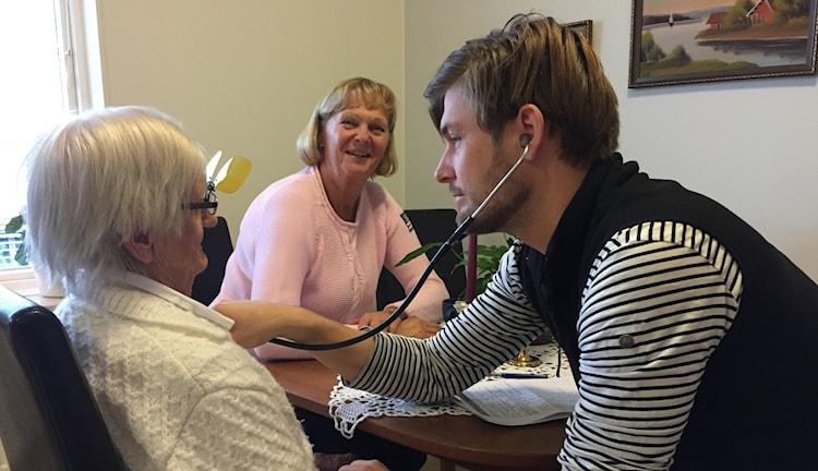 Läkaren Martin Franzelius lyssnar på Astrid Johanssons hjärta. Dottern Elisabeth Johansson tittar på.