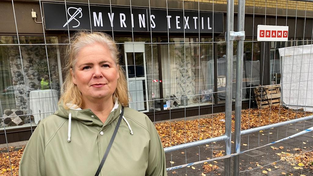 En kvinna står framför en rökskadad textilbutik i Annedal i Göteborg.