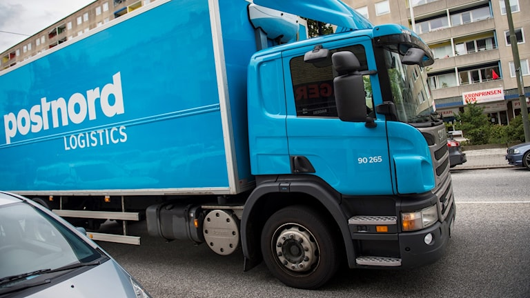 En blå bil som det står postnord på
