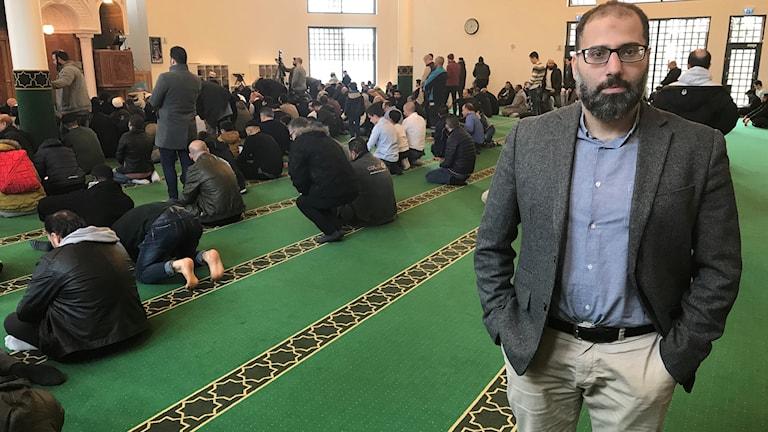 En man står i en moske´. Bakom honom ses män som ber på golvet.