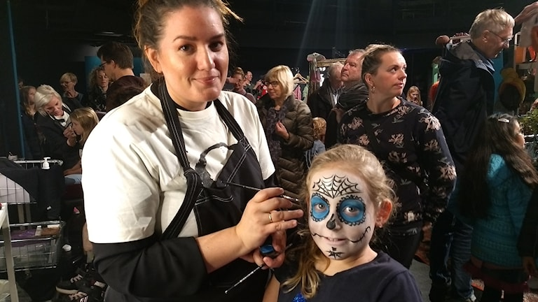 En tjej sminkar en flicka i ansiktet så att hon ser ut som en döskalle med blåfärgade ögonhålor.