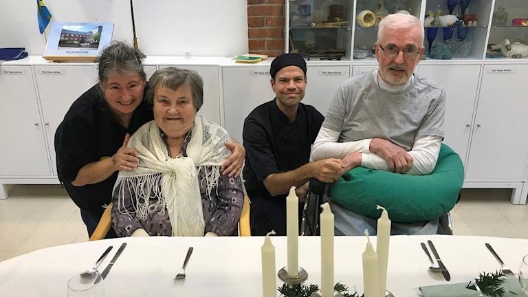 Två kvinnor och två män vid dukat bord på äldreboende.