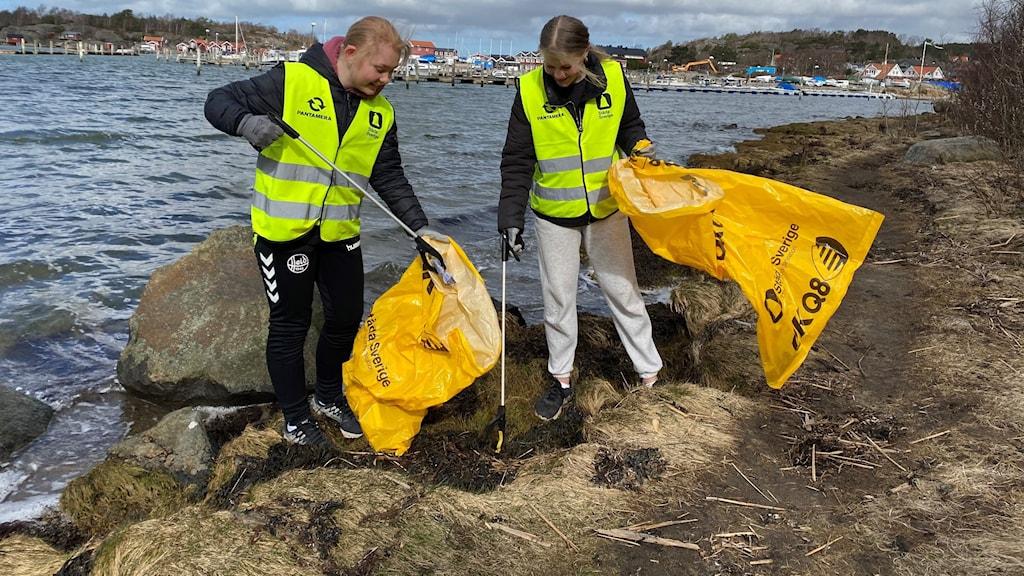 Två flickor i gula västar plockar skräp i i gula plastsäckar vid havet.