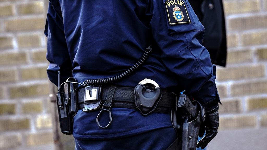 Torso av person klädd i blå polisuniform.
