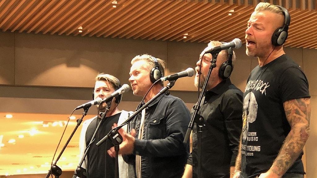 fyra män sjunger på en scen