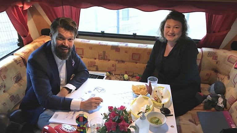 Niklas och Ina sitter i en soffa i husvagnen. De har lite tacos-rester på bordet, rosor och lite annat.