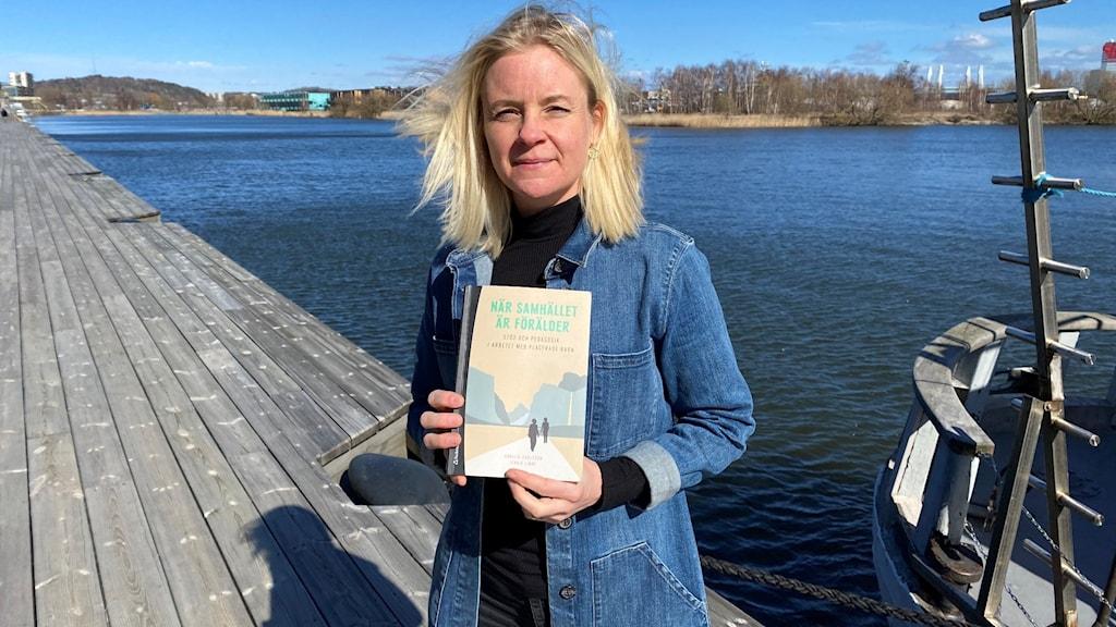Kvinna i solen som håller upp en bok framför vattnet.
