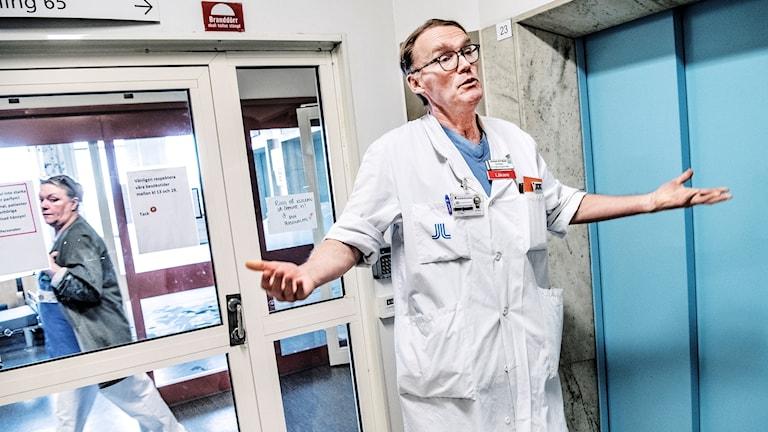 En läkare som slår ut med händerna