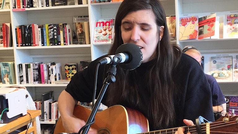 En tjej med långt mörkt hår spelar på en gitarr och sjunger i en mikrofon.