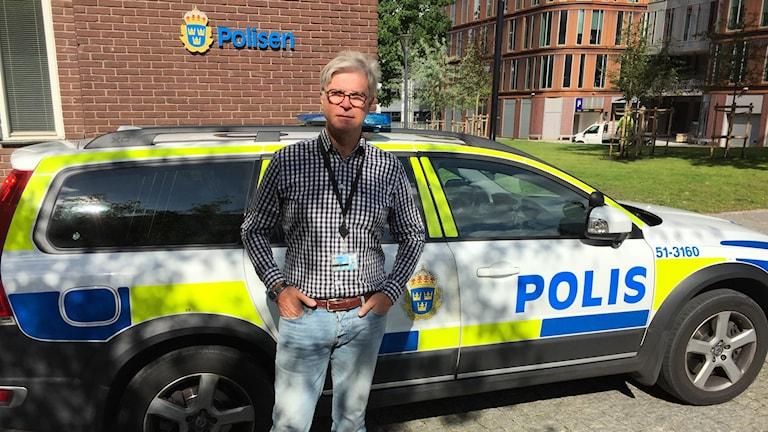 Brottssamordnaren Olle Carlström står framför en polisbil