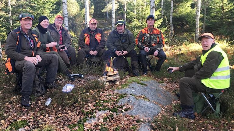 Sju män sitter kring en lägereld i skogen.